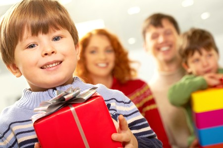 Portrait of smiling boy with gift looking at camera on background of family  photo