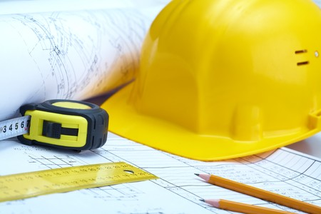 housebuilding: instruments of builder over plan of house