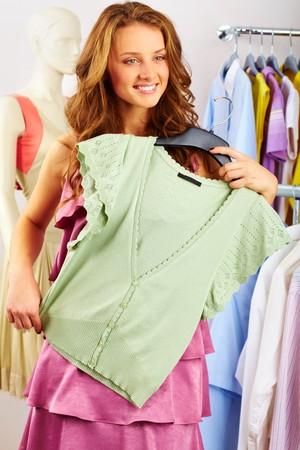 blusa: Una chica que se trata de una camiseta en la tienda
