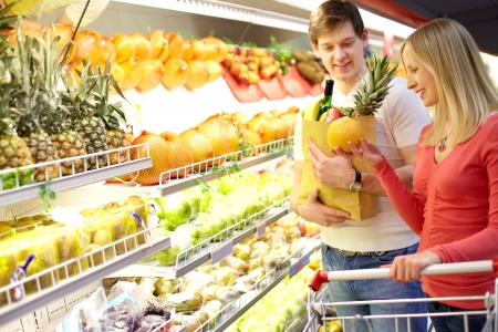 Portrait of couple choosing fruits in supermarket  photo