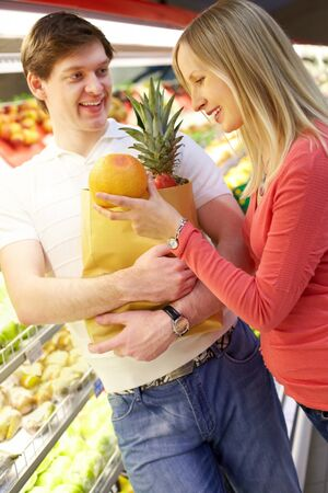Portrait of woman putting orange into shopping bag held by smiling man in supermarket Stock Photo - 7964857