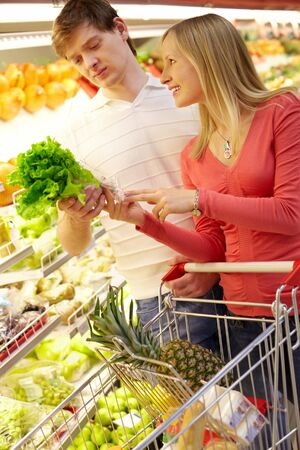 Portrait of happy couple choosing greenery in supermarket Stock Photo - 7964869