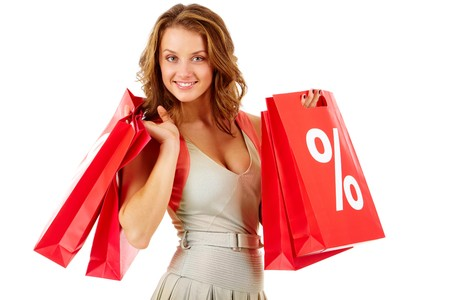 Portrait of a girl holding handbags with discount symbol, looking at camera and smiling Stock Photo - 7964888