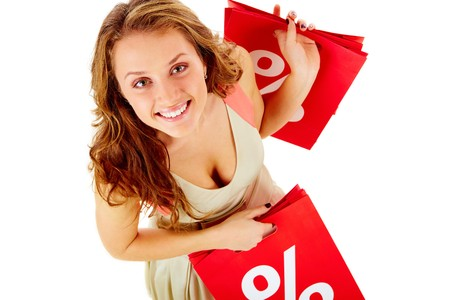 Above view of a girl holding paper bags with discount symbol, looking at camera and smiling Stock Photo - 7964914