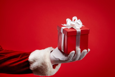 An image of Santa's hand holding a gift box against red background
