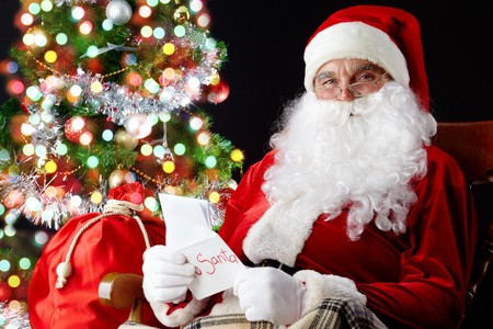 Santa sitting at the Christmas tree, holding Christmas letters and looking at camera  photo