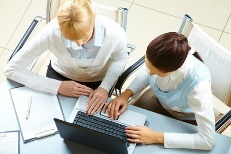 Above view of two businesswomen typing on a laptop photo