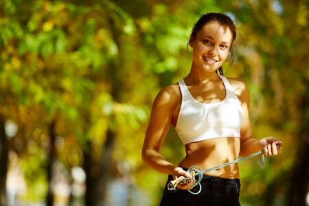 A young woman holding a skipping rope, looking at camera and smiling against natural background Stock Photo - 7965320