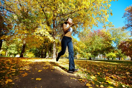 A young girl running in autumn park Stock Photo - 7965414