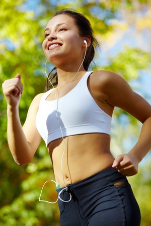 activewear: Portrait of a young woman jogging with a player