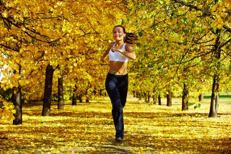 joggers: A young girl jogging among golden autumn trees