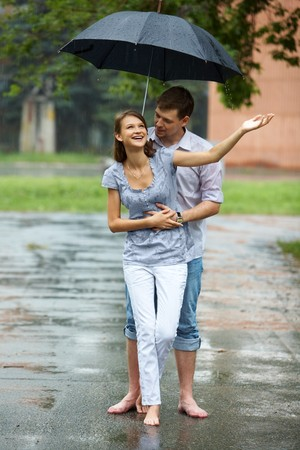 A young couple walking in the rain barefoot Stock Photo - 7965301