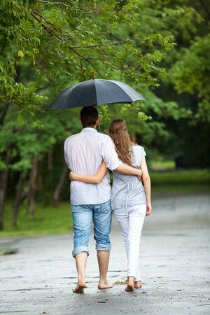 Rear view of a couple walking in the rain under umbrella and hugging photo