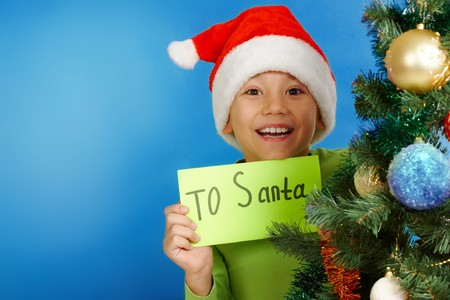 Image of happy boy showing letter with note �To Santa� on a blue background  photo