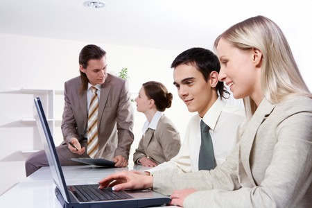 Four young businesswomen sitting at table, two of them working with a laptop Stock Photo - 7965245