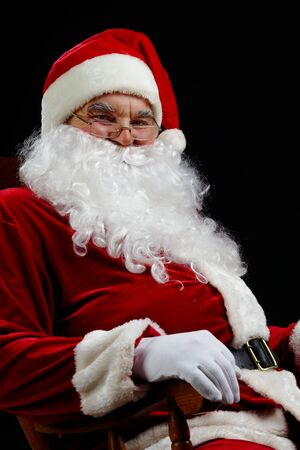 Santa sitting and smiling isolated on black Stock Photo - 7965352