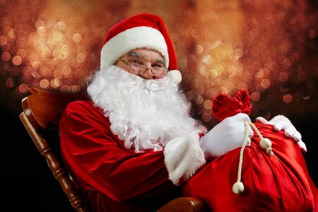 Santa sitting with a sack against glaring lights Stock Photo - 7965339