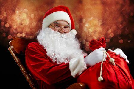 glaring: Santa sitting with a sack against glaring lights