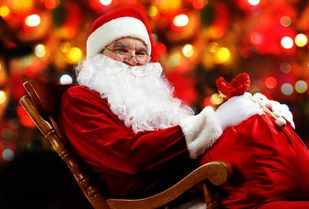 Santa sitting with a sack against sparkling lights photo