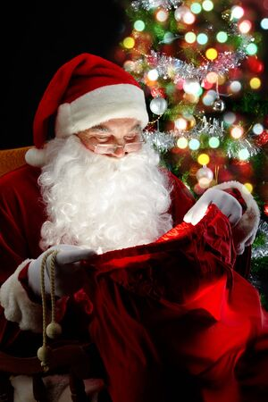 Santa sitting at the Christmas tree and looking into the sack  photo