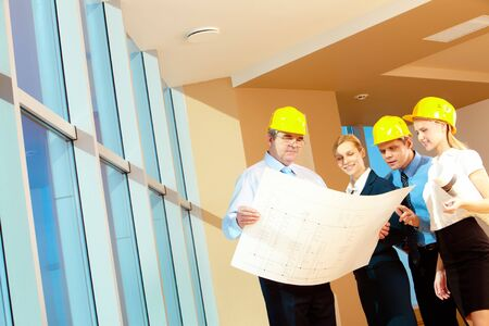 Portrait of team of workers holding a project and discussing it Stock Photo - 7965334