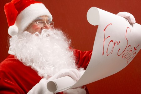 Portrait of cute Santa Claus reading big letter on red background photo