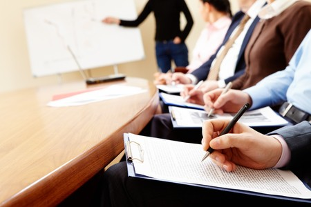shorthand: Close-up of businesspeople hands holding pens and papers near table at business seminar   Stock Photo