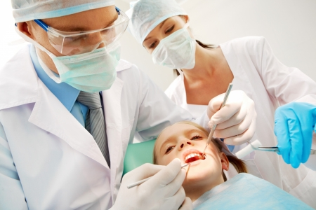 curing: A dentist and a nurse curing little girl�s teeth