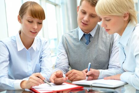 Image of business people consulting during paperwork photo