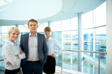 next to each other: Portrait of smart business people standing next to each other and looking at camera