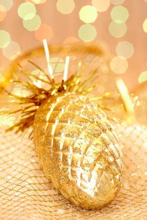 Golden Christmas pinecone against glaring background photo