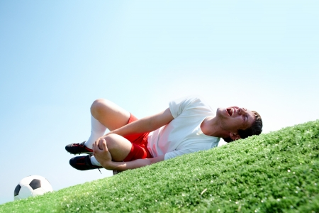 Image of soccer player lying down and shouting in pain photo