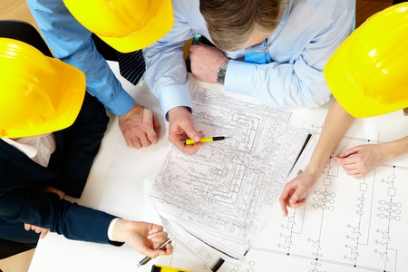 engineer: Above view of four architects sitting at the table and discussing design project Stock Photo