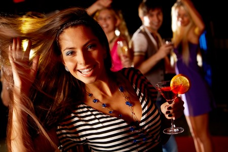 Portrait of cheerful girl dancing at party while smiling at camera photo