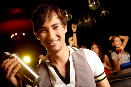 Portrait of smiling male with bottle looking at on background of dancers Stock Photo - 8015661