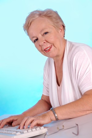 Portrait of friendly aged woman typing and looking at camera Stock Photo - 8015657