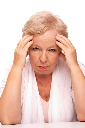 a year older: Portrait of sick aged woman touching head and looking at camera Stock Photo