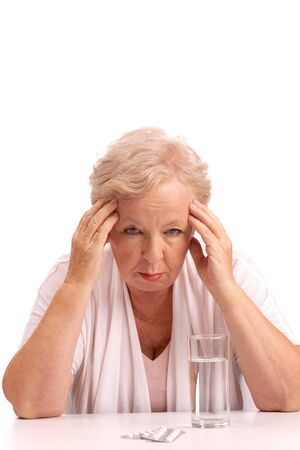 Portrait of sick aged woman touching head with tablets near by photo
