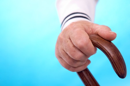 incapacity: Vertical image of elderly human hand leaning on cane handle Stock Photo