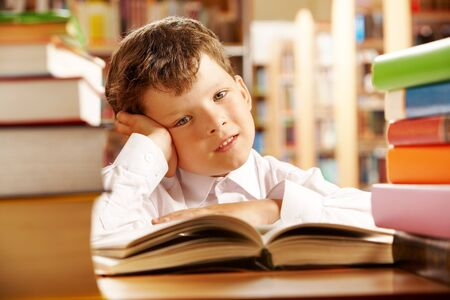 Portrait of a schoolboy sitting at table piled with books photo