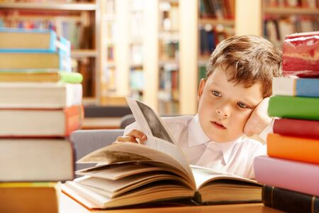 A schoolboy sitting in the library and turning the pages over  photo