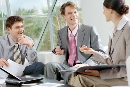 Three businesspeople sitting at table and communicating  Stock Photo - 8015676