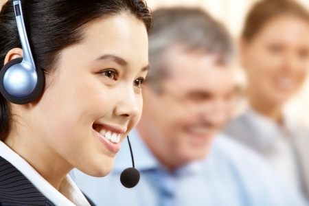 customer service representative: A young switch operator smiling against her two colleagues