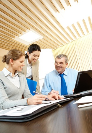 Three businesspeople sitting in the office and smiling photo