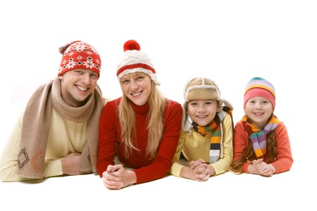 A family of four in warm clothing lying isolated on white photo