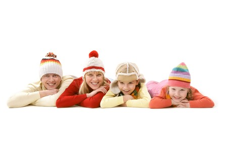 A family of four in warm clothes lying and smiling isolated on white photo