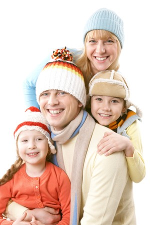 A family of four in winter clothes smiling and looking at camera  photo