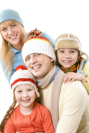 A happy family of four in warm clothes embracing  photo