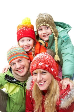 ropa de invierno: Familia feliz en ropa de invierno mirando a la c�mara y sonriente  Foto de archivo