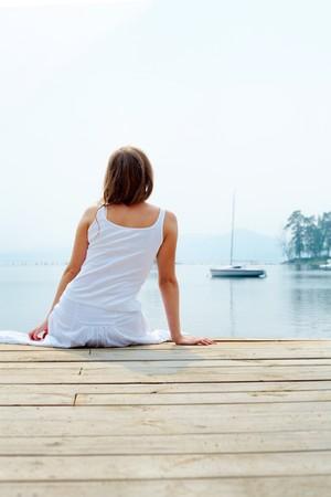 mujeres sentadas: Vista posterior del bastante joven dama en ropa de algod�n blanco tener resto por la orilla del mar